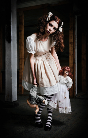 The strange scary girl with dolls in hands