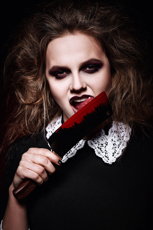 woman knife: Horror shot: a scary evil girl licking bloody knife