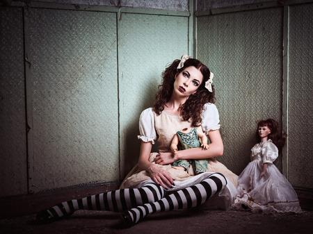 Strange sad girl with dolls sitting in the forsaken place Stock Photo