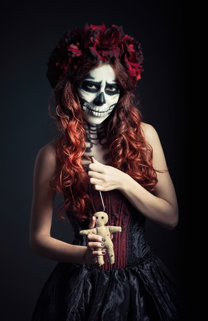 voodoo: Young voodoo witch with muertos makeup (sugar skull) holds voodoo doll and needle Stock Photo