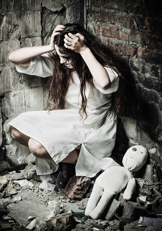 madhouse: Horror style shot: the strange crazy girl and her moppet doll