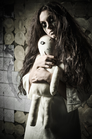 Horror style shot: a strange sad girl with moppet doll in hands 스톡 콘텐츠