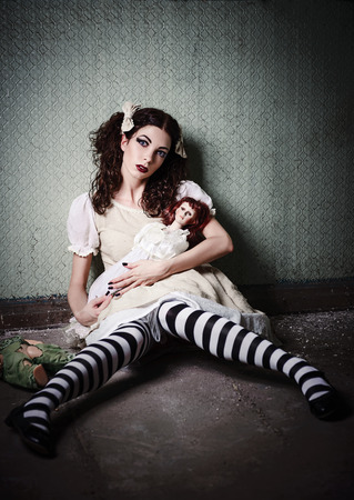 madhouse: Weird sad young girl with dolls sitting in a dirty room Stock Photo