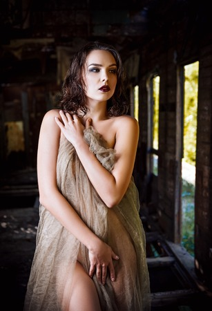 Sexy beautiful young woman covered in cloth stands in the old train wagon