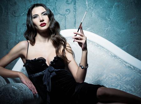 소파와 흡연 담배에 누워 매력적인 젊은 여자. 레트로 스타일