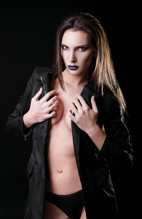 Studio fashion shot: a gorgeous sexy young woman wearing black panties and jacket