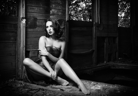beautiful sad: Beautiful young sad girl covered in cloth sits in the old train wagon. Black and white photo Stock Photo