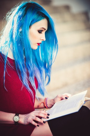 Beautiful young girl with blue hair sitting on stairs and reading a book. Closeup Stock Photo