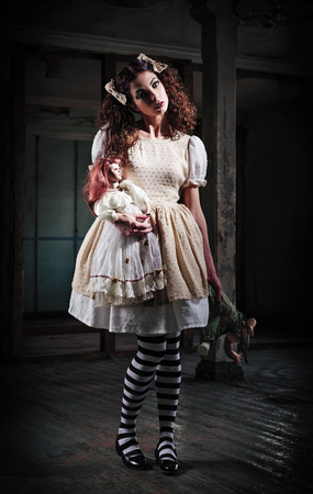 Weird girl with dolls in the abandoned place