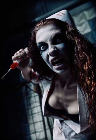 Horror shot: the crazy evil nurse (doctor) with syringe in hand. Zombie woman (living dead)