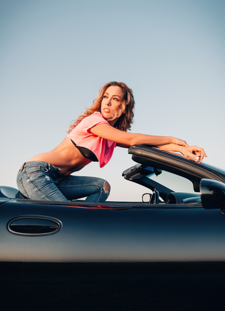 Sexy beautiful young girl dressed in jeans and topic sitting in the car (cabriolet). Outdoor portrait at sunset