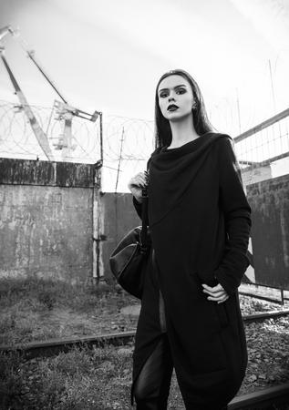 Ritratto della bella ragazza rock (modello informale) in tunica e pantaloni di pelle in piedi in zona industriale. Bianco e nero Archivio Fotografico - 89549793