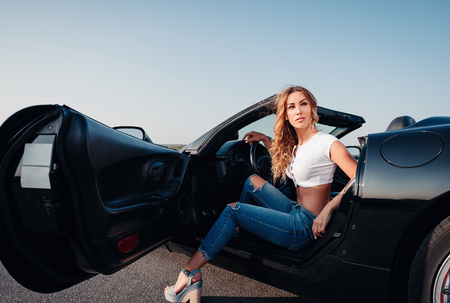 Sexy beautiful young girl dressed in jeans and topic sitting in the car (cabriolet). Outdoor portrait on a road