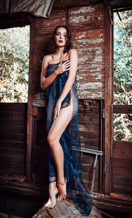 Sexy beautiful young girl covered in fabric stands in the old train wagon. Full length
