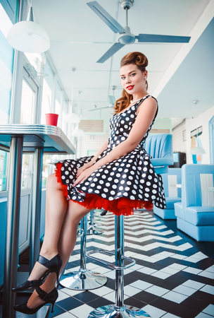 Retro (vintage) portrait of the smiling cute young girl sitting in cafe. Pin up style portrait of young girl in dress Stock fotó