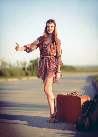 Attractive smiling young hippie woman hitchhiking on the road at sunset time