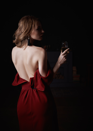 Gloomy mysterious portrait of the alluring beautiful young woman in downcast red dress with a goblet of champagne in hand. Rear view