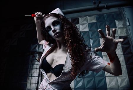 Tir d'horreur: l'horrible infirmière folle et méchante (médecin) en uniforme sanglant tuant à la seringue. Femme zombie (morte-vivante). Monstre du cauchemar Banque d'images