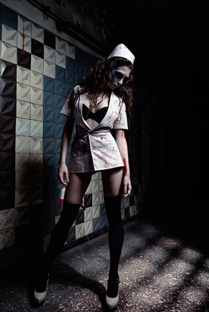 Horror shot: the spooky mad nurse (doctor) with bloody syringe in hand. Zombie woman (living dead) Фото со стока