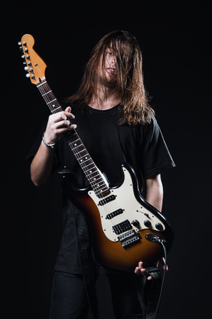Studio portrait: a handsome young man with long hair (rock musician) holds electric guitar in hands Reklamní fotografie