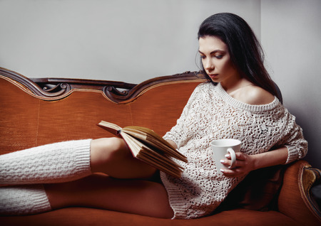 Portrait of beautiful young woman dressed in sweater and knee socks. Alluring girl with cup in hand lying on a sofa and reading book