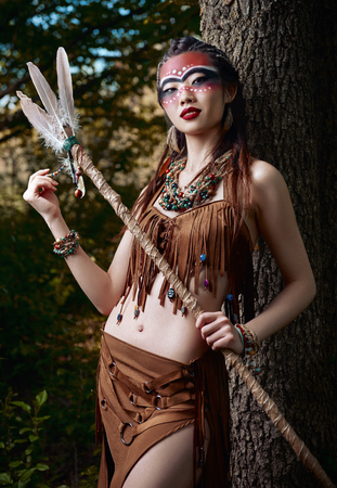 Outdoor portrait of the beautiful young shamaness (witch doctor) with stick. Cute smiling shaman (sorceress) stands at the tree in forest Stok Fotoğraf