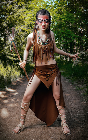 Outdoor portrait of the young shamaness (witch doctor) in forest. Aggressive shaman (hex) preparing for battle