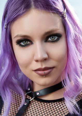 Close-up portrait of the beautiful smiling gothic girl. Pastel goth with violet (pink) hair