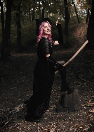 Halloween theme: modern smiling young witch in black dress and hat with broom in a dark forest