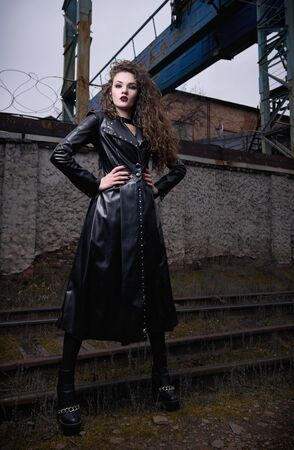 Fashion shot: portrait of a cool rock girl (informal model) in leather coat standing at railroad (industrial area)