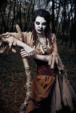 Halloween theme: wicked scary voodoo witch with staff. Portrait of the evil sorceress in dark grove. Zombie woman (undead) 스톡 콘텐츠