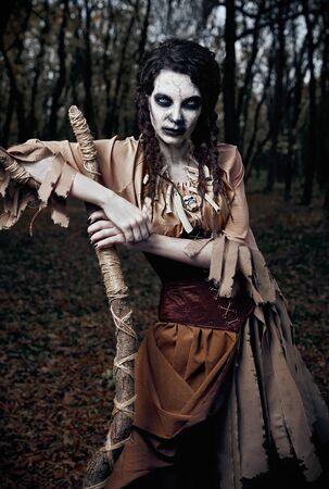 Tema de Halloween: malvada bruja vudú aterradora con bastón. Retrato de la malvada hechicera en bosque oscuro. Mujer zombi (no muerta) Foto de archivo