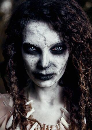 Tema de Halloween: espeluznante bruja vudú sombría. Retrato de primer plano de la malvada hechicera. Mujer zombi (no muerta) Foto de archivo