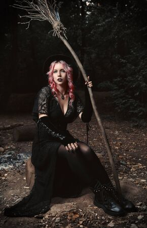 Halloween theme: contemporary young witch in black dress and hat with broom sitting in a dark grove