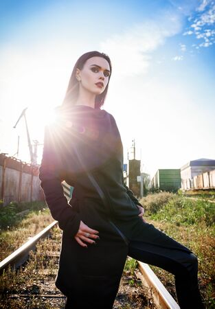 Fashion shot: portrait of the attractive rock girl (informal model) in tunic and leather pants standing at railroad (industrial area)