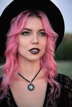 Halloween theme: beautiful young pink-haired witch in black dress and hat. Close-up portrait