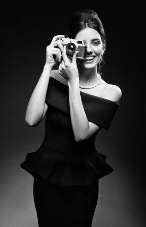 Retro shot: the beautiful young woman shooting by old film camera. Vintage portrait of smiling gorgeous girl in 60s style. Elegant lady in black dress and pearl necklace. Film grain effect, black and white