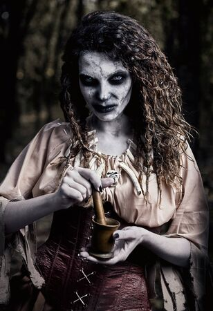 Halloween theme: ugly terrible voodoo witch with mortar and pestle. Portrait of the evil hag in dark forest. Zombie woman (undead)