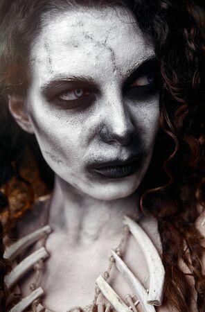 Tema de Halloween: bruja vudú malhumorada aterradora. Retrato de primer plano de la bruja malvada. Mujer zombi (no muerta)