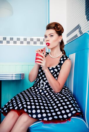 Retro (vintage) portrait of the beautiful young girl sitting in cafe and drinking beverage. Pin up style portrait of young girl in dress Stok Fotoğraf