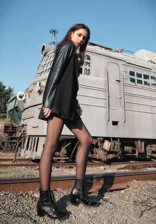 Fashion shot: portrait of the lovely rock girl (informal model) dressed black in jacket and skirt standing at railroad (industrial area) Stock fotó