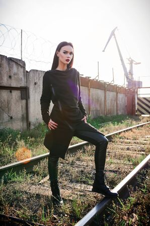 Fashion shot: portrait of the lovely rock girl (informal model) in tunic and leather pants standing at railroad (industrial area)