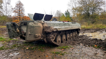 A combat vehicle before start to race in deep mud.