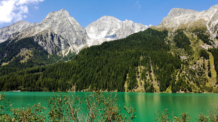 A lake in the mountains with gree water.