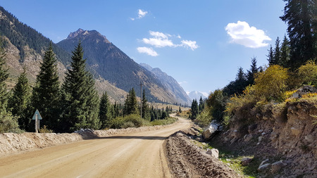 A gravel road to the moutains under blue sky with clouds. Reklamní fotografie