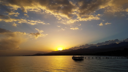 A sunset above lake with pier and mountains with blue sky and clouds. Reklamní fotografie