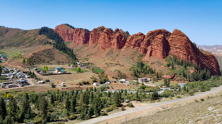 A red rocks under blue sky with green trees and houses.