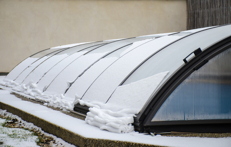 Melting snow on the pool roof going down. Reklamní fotografie