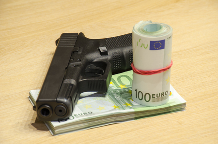 The pistol with bullets stays behind money with bllured wall backspace.