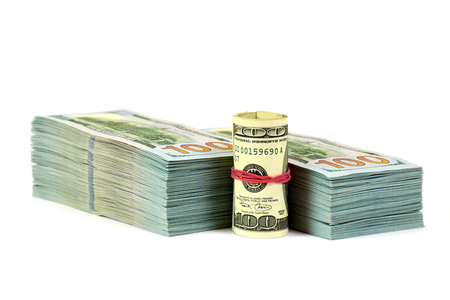 A stack of money with a roll front of it isolated in white background.